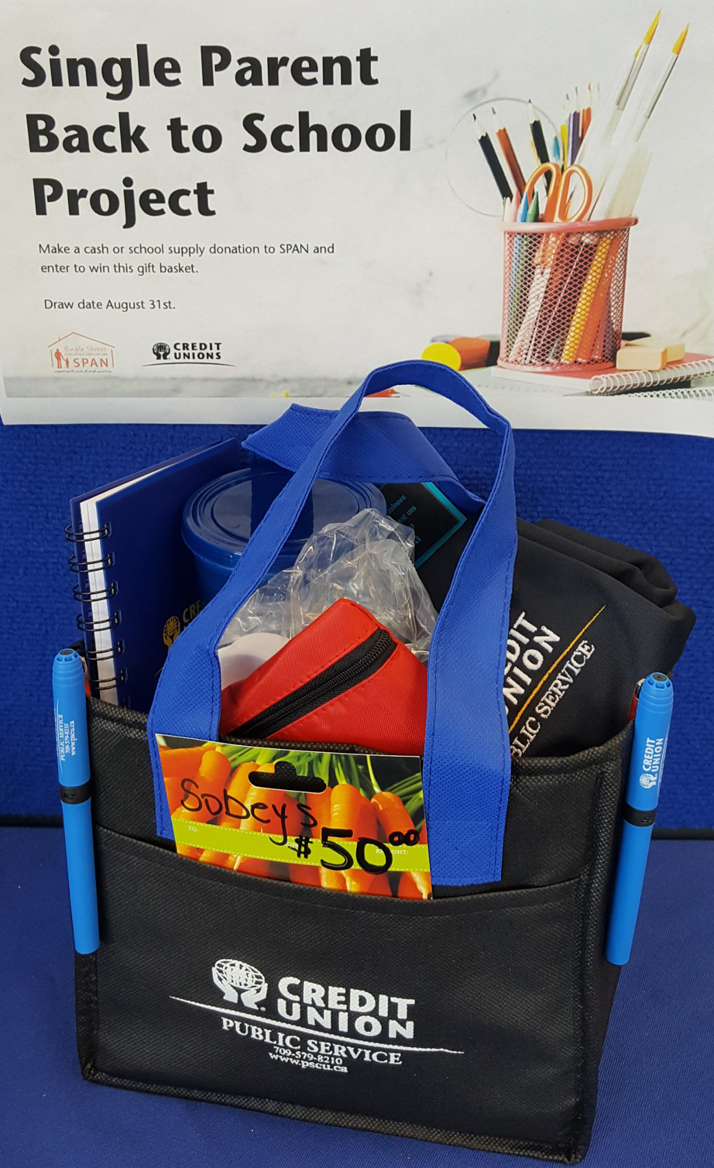 PSCU SPAN Prize Pack. The prize consists of a $50.00 Sobeys gift card, PSCU lunch bag, Ladies golf shirt, tumbler, hardcover note book and pens, ear buds, desk calendar and a mini travel first aid kit.
